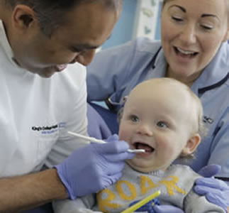 Dentist with smiling toddler and nurse